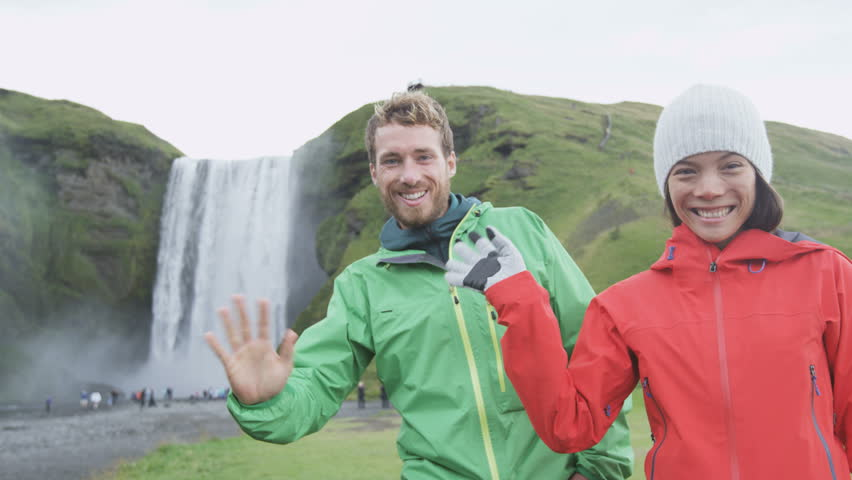 People waving hello with hand by Skogafoss waterfall on Iceland on ring road. Happy couple looking at camera saying hi and welcome visiting tourist attraction landmarks in Icelandic nature. RED EPIC