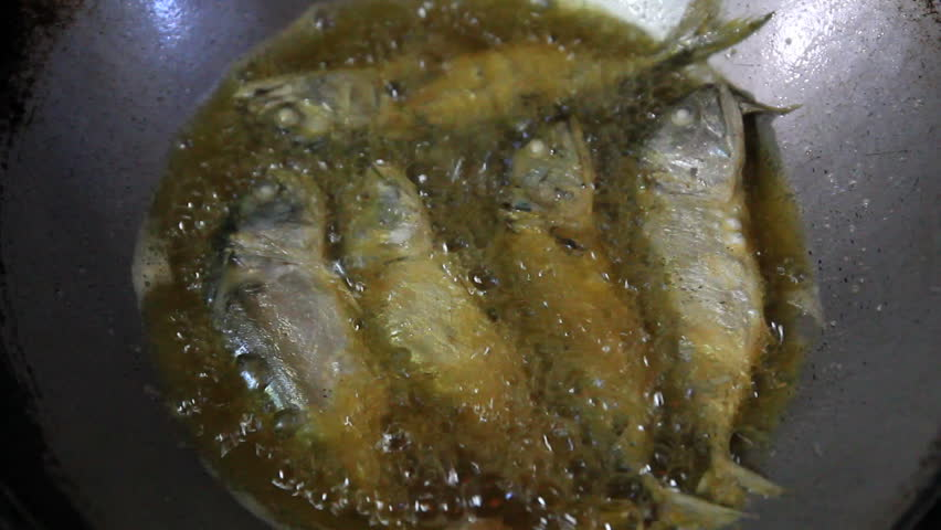 Frying mackerel fish in pan with vegetable oil stock for Best oil for frying fish