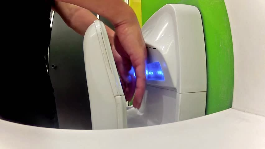 man dry hands on modern hand dryer in toilet