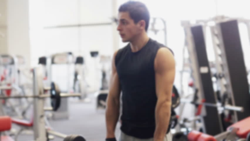 sport, bodybuilding, lifestyle and people concept - young man with dumbbell flexing muscles in gym - HD stock footage clip