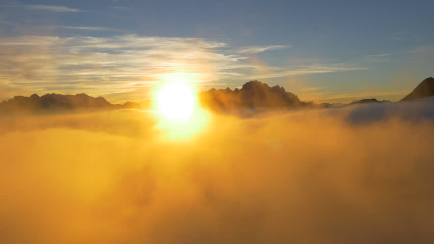 AERIAL: Rising through the clouds into the spectacular sunset
