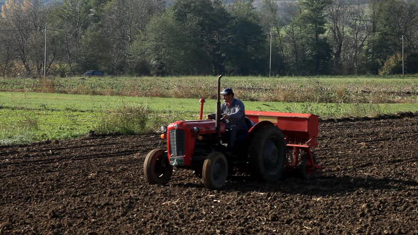 Tractor In Field Planting : Farm tractor working the ground stock footage video