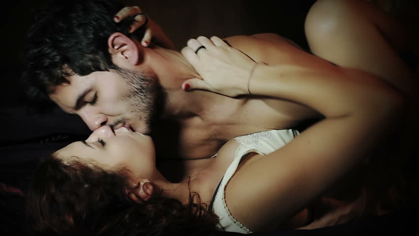 Sexy young couple kissing and playing in bed