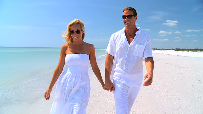 Attractive young caucasian couple in love walking together on the beach 60FPS - HD stock video clip