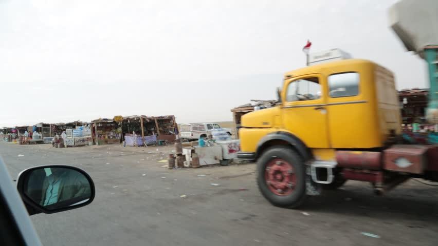 Basra, Iraq, October 2014: Point of View Passing Shot from Vehicle at Makeshift Dukas (Shops) Along Iraqi Highway in Basra, Iraq, October 2014.