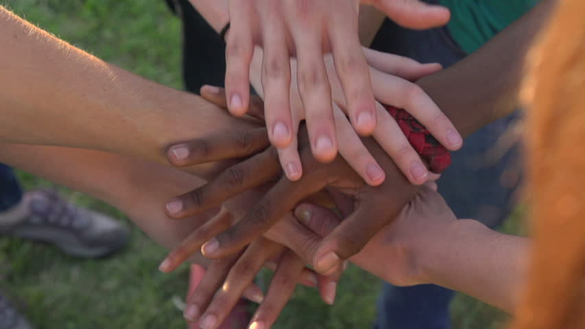 A close-up in slow motion, of hands of all races and colors stacked together one by one in unity and teamwork and then raised.