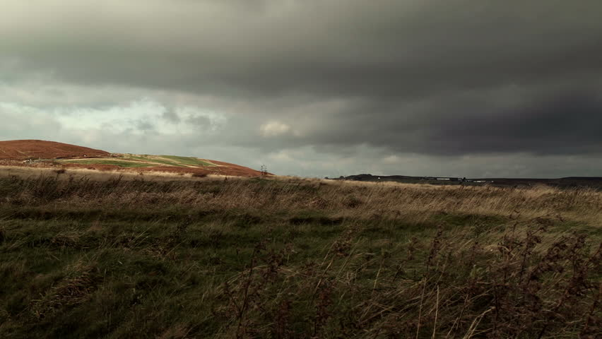 Menacing Moorland Landscape HD Stock Footage. A dramatic Moorland landscape with a breezy foreground Foliage and a hostile stormy sky.
