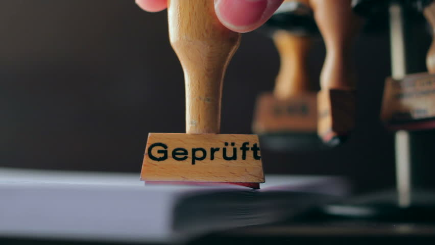 Rubber stamp on office desk. The translation of the german letters Geprueft is approved
