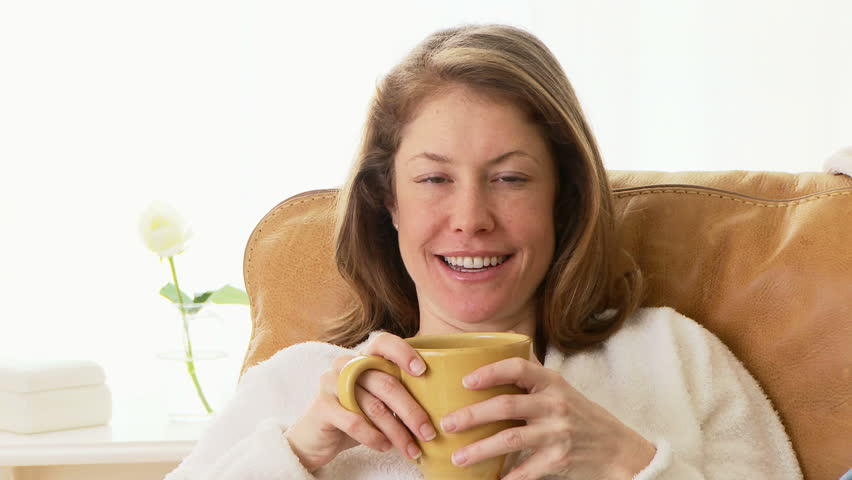 Woman sitting on couch drinking coffee - HD stock footage clip