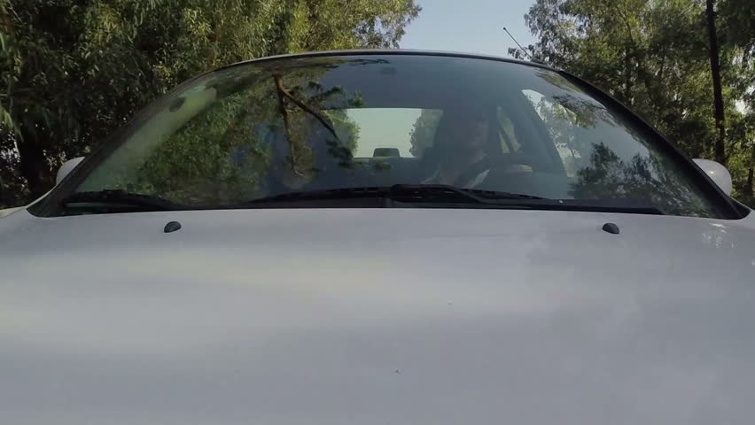 Couple driving car fixed camera. Windshield front view.