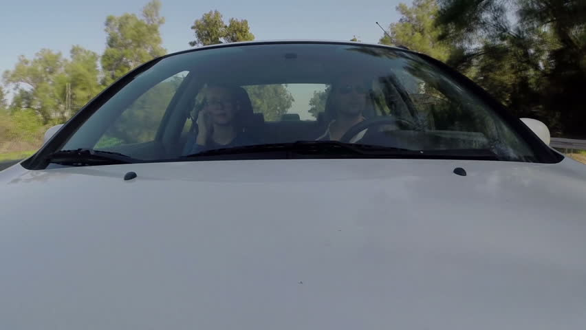 Couple driving in the car. Fixed front shot. Country road