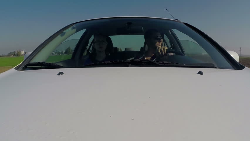 Couple driving car. Front windscreen view. Fixed shot