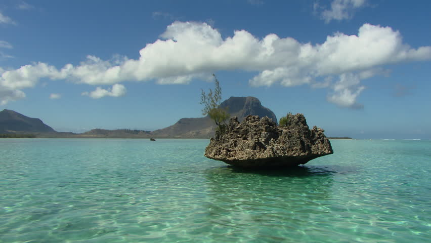 POV shot of rocks and mountains in sea in mauritius