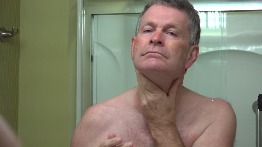 Senior man looks in mirror in bathroom, smiles thumbs up - HD stock video clip