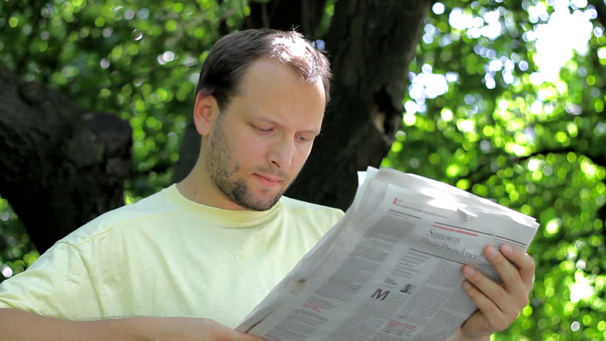 Man reading newspaper in the park - 1080p - HD stock video clip