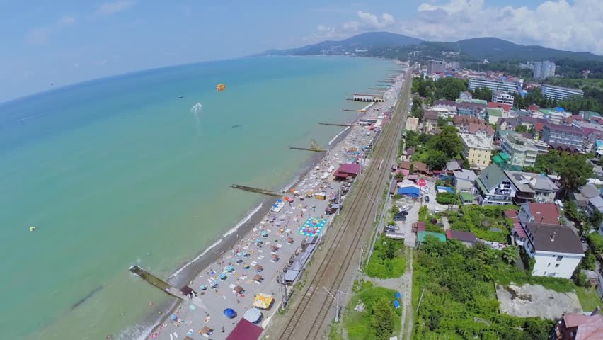 Man flies on parachute above sea near coastal town with many tourists get rest on beach at summer sunny day. Aerial view - HD stock video clip