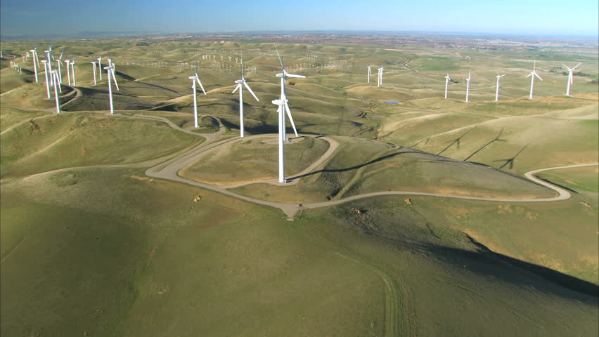 Low aerial view of cluster of wind turbines in green hillside - HD stock video clip