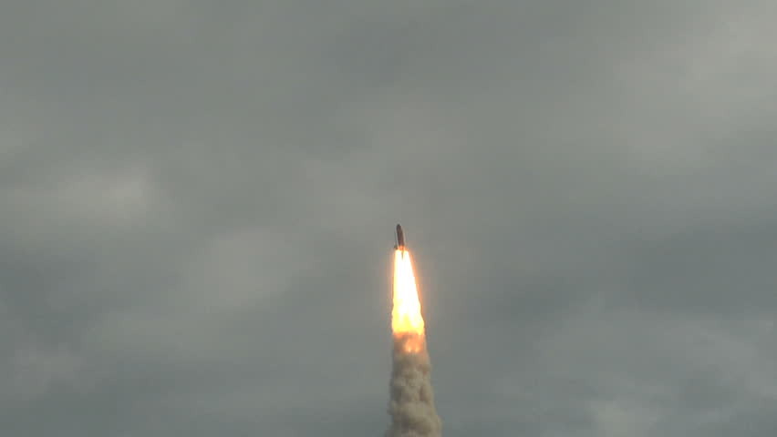 Space Shuttle launches through the clouds.