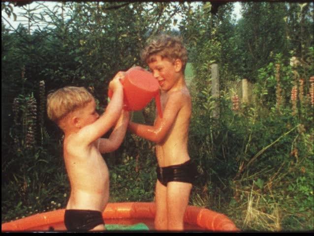 Children splashing in garden pool (vintage 8 mm amateur film) - HD stock footage clip