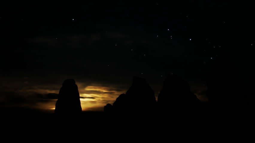 Astrophotography time lapse footage with pan right motion of moon rising over monolithic formation in the desert of Trona, California