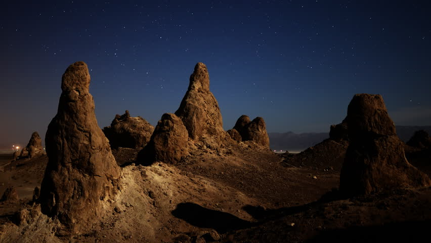 4K astrophotography time lapse with zoom out motion of night to day transition over eroded formation in Trona Pinnacles, California