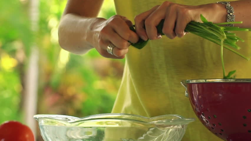 Woman hands tearing spinach leaves into glass bowl, slow motion shot at 120fps