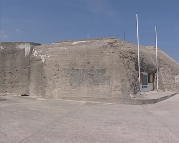 NORMANDY, FRANCE - JUNE 2005: Arromanches, France - Atlantic Wall, German Casemate + pan Gold Beach and ocean. Gold Beach was the code name of one of the D-Day landing beaches. - SD stock footage clip
