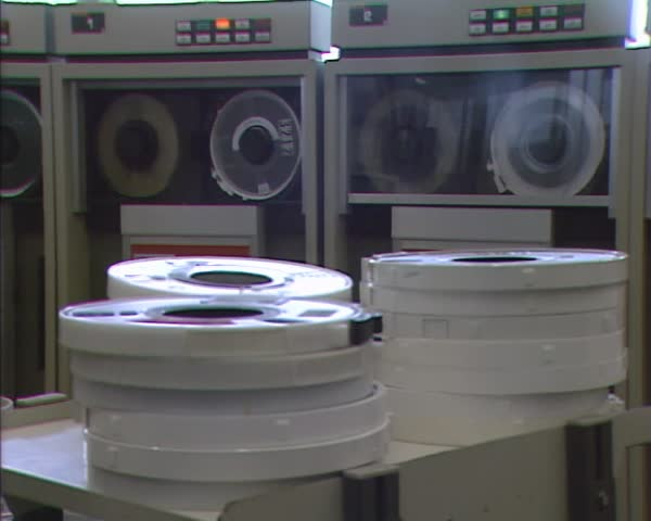 GRONINGEN, THE NETHERLANDS - 1980s:  Spinning magnetic tape in mainframe computer room, pile of magnetic tapes in front.