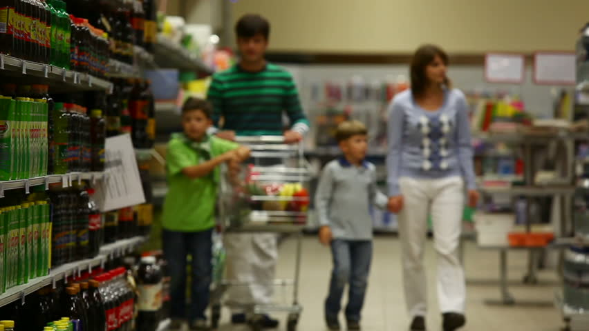 A family of four walking along the beverage row in the supermarket, the sons putting drinks into the trolley