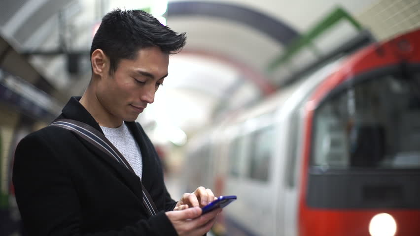 Young Asian man using his phone in a subway station as his train arrives