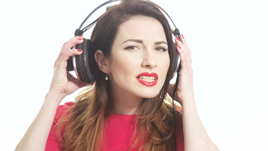 Pretty woman wearing red lipstick listening to the music touching big headphones takes off ear cup saying what isolated on white background close up shot