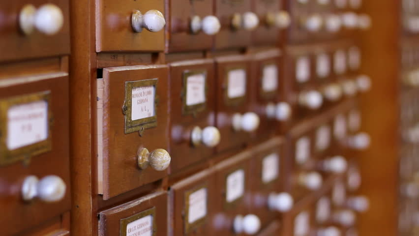 A hand opens a drawer and browse with fingers through the cards arranged alphabetically for a certain sheet informations, after it close the tray, in an old library.