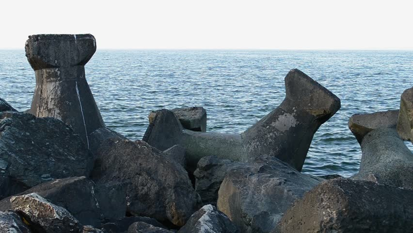 Concrete cast designs of large stones made as  breakwater constructions, for preventing big waves to crush shore. Sound included.