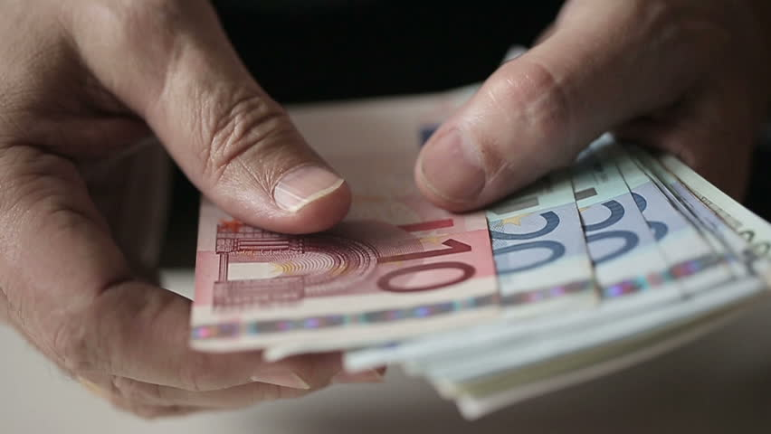 Old man's hands counting euro banknotes. Slow motion. Close up