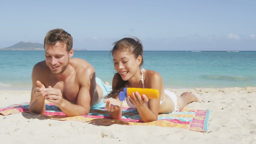 People on beach putting sunscreen suntan lotion. Sun tanning couple having fun laughing and relaxing on vacation. Adults, Asian woman and Caucasian man lying down in white sand on beautiful beach.