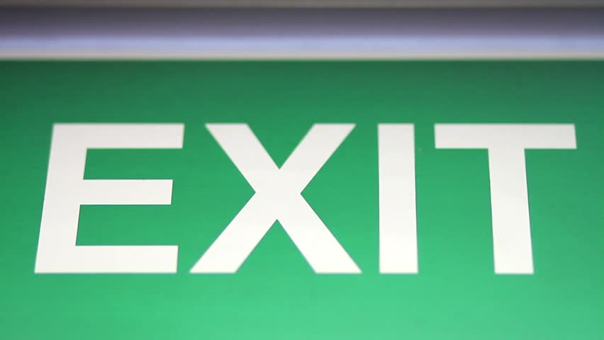 An emergency exit sign goes into focus and out of focus/We have to go this way