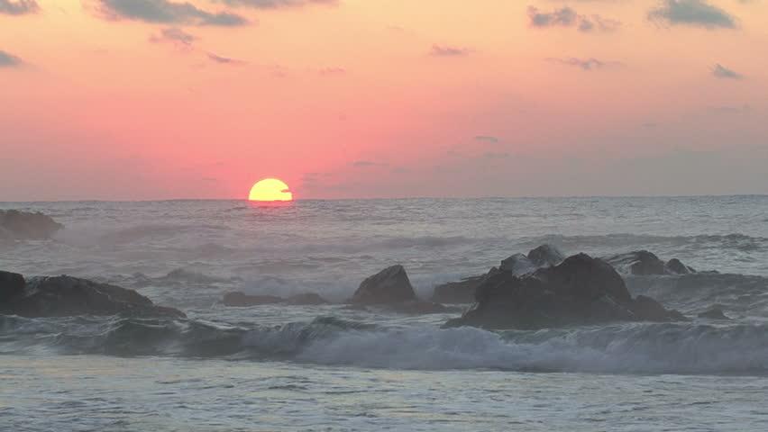 Sunrise on the beach rocks - Tranquil idyllic scene of a golden sunset over the sea, waves slowly splashing on the sand, sea rocks and drifting fog on the background