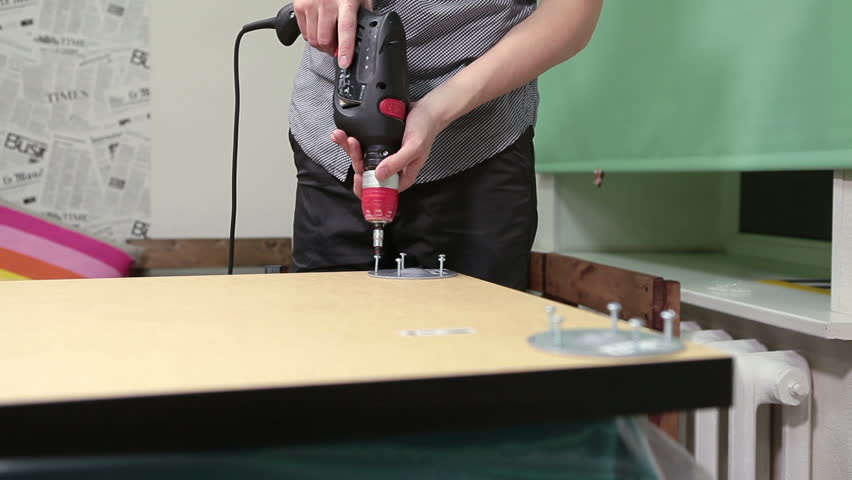 Worker using electric drill for furniture construction