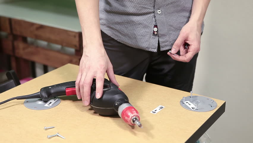Human hands take in screws in tabletop for spinning with electric drill, table legs holders installing