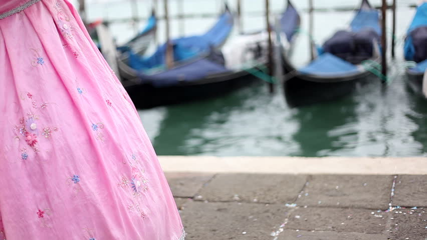 Unrecognizable pink carnival mask standing in front of venetian lagoon and gondolas.