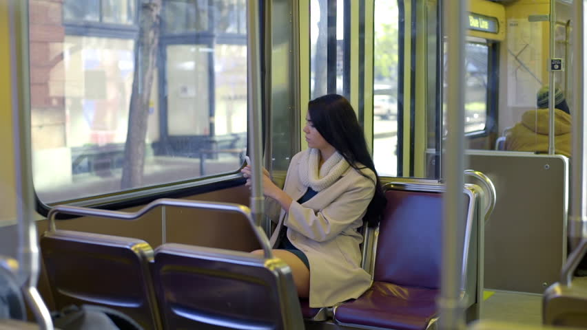 Teen, On A Train, Takes A Phone Pic Out Her Window At A Train Stop In The City