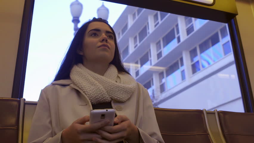 Backlit Mixed Race Young Woman Rides The Train In The City, And Texts On Her Smart Phone