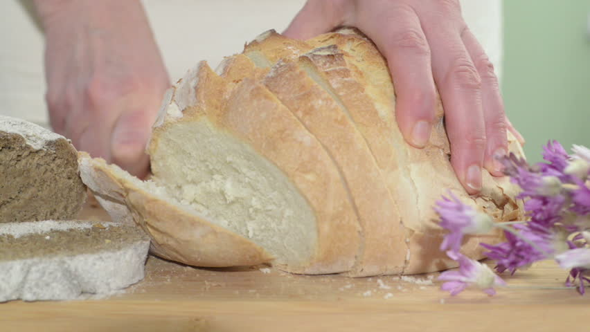 Close up of bread knife slicing through a baguette with sesame seeds