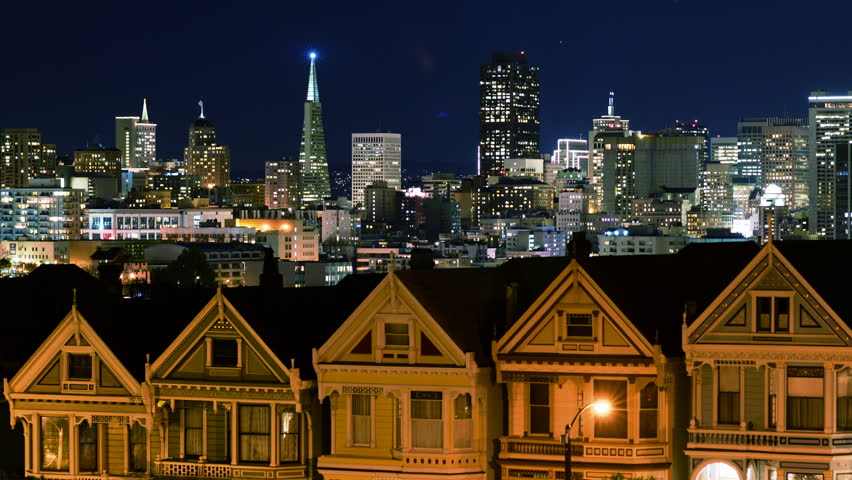 """4K Time lapse footage of iconic """"Postcard Row,"""" traditional Victorian style houses and skyline at night in San Francisco, California"""