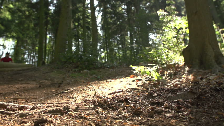 Slow motion sequence of man riding mountain bike making dramatic mid-air jump on woodland trail towards camera against sun.Shot on Sony FS700 at a frame rate of 100fps