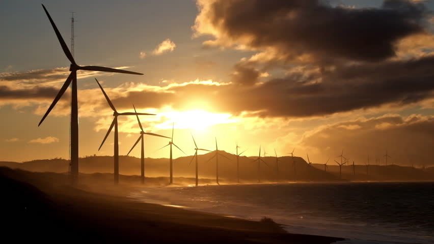 Wind turbine power generators silhouettes at stormy ocean coastline at sunset. Alternative renewable energy production in Philippines - HD stock video clip