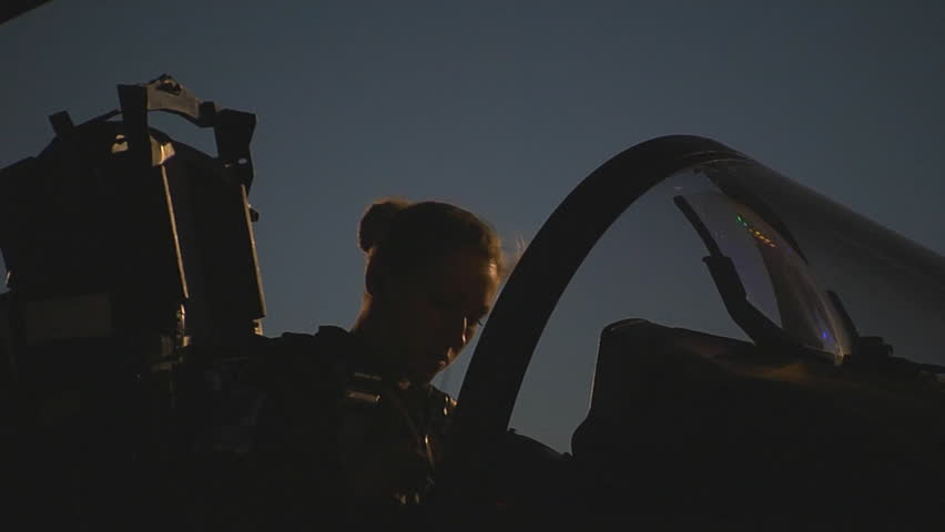 CIRCA 2010s - A female pilot dons her helmet in a jet fighter.