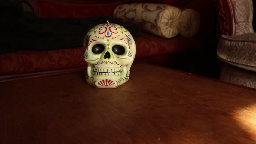 DOLLY MOVE WITH SKULL: Skull is Cinco de Mayo style, made of Wax, on Wooden table with Vintage couch  / CURRENT VARIATION: Dolly out to reveal skull, hold on medium shot; then continue pulling back  | Shutterstock HD Video #9100637