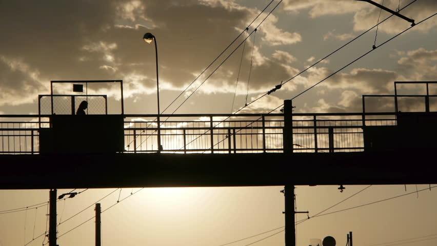 Silhouettes of people crossing railway on the old steel bridge