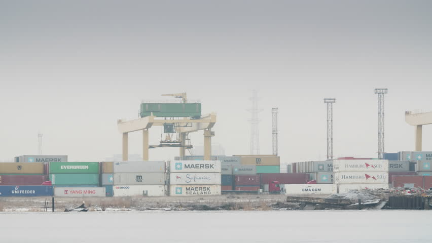 Medium shot time lapse of container handling gantry cranes arranging containers in the Freeport of Riga, Latvia